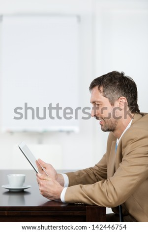 Mature businessman reading message at digital tablet in office