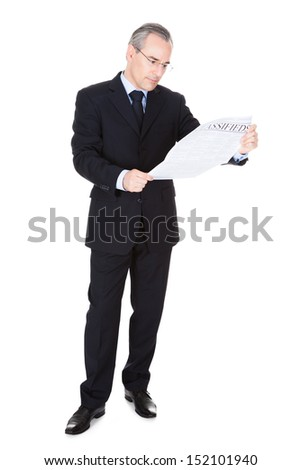 Mature Businessman Reading Newspaper Over White Background - stock photo