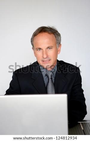 Mature businessman sat at desk - stock photo