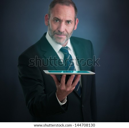 Mature businessman serving with tablet PC , looking into the camera - stock photo