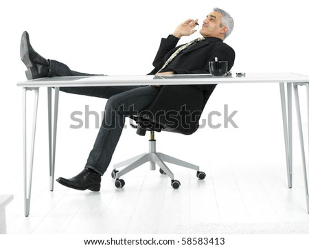 Mature businessman sitting at desk in confident pose, smoking cigar. Isolated on white.