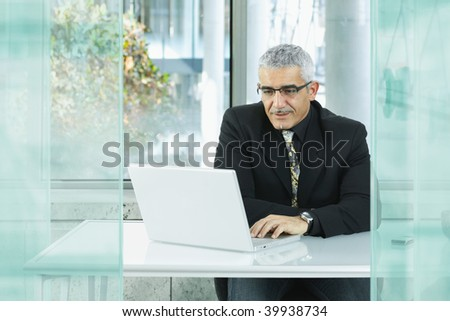 Mature businessman sitting at desk in modern office, using laptop computer.