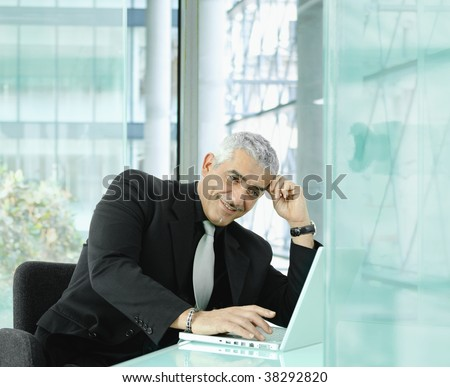 Mature businessman sitting at desk in modern office, working with laptop computer, smiling.