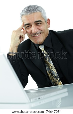 Mature businessman sitting at desk, using laptop computer, smiling. Isolated on white.?
