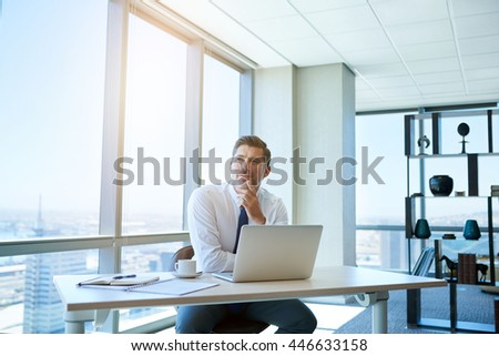 Mature businessman sitting at his desk in his office with large windows, his laptop open on front of him and looking away with a thoughtful and positive expression - stock photo