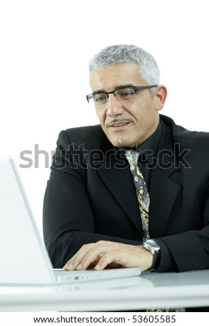 Mature businessman sitting at office desk, working with laptop computer. Isolated on white.
