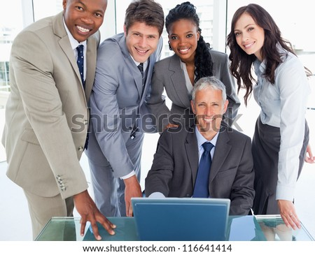 Mature businessman sitting at the desk surrounded by his smiling team