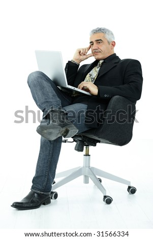 Mature businessman sitting in office chair working on laptop computer, serious look, isolated on white background.