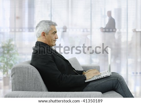 Mature businessman sitting on couch in modern office, using laptop computer.