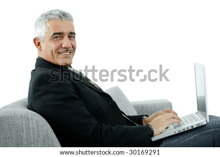 Mature businessman sitting on sofa, using laptop computer, smiling. Isolated on white. - stock photo
