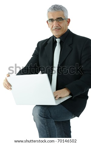Mature businessman standing, holding laptop computer on his knee. Isolated on white.? - stock photo