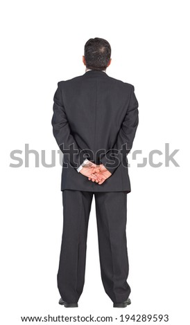 Mature businessman standing with hands behind back on white background