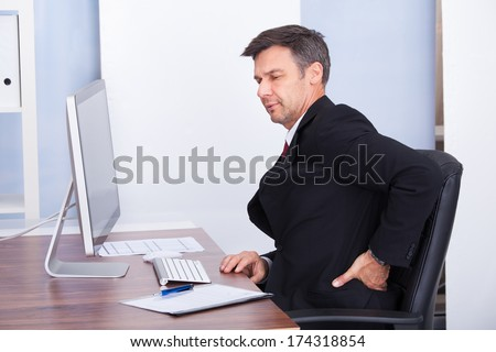 Mature Businessman Suffering From Back Pain While Working In Office - stock photo
