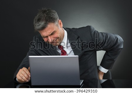 Mature Businessman Suffering From Back Pain While Working On Laptop At Desk - stock photo