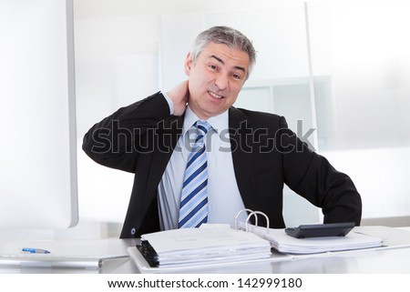 Mature Businessman Suffering From Neck Pain At Office - stock photo