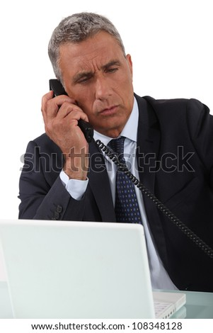 Mature businessman taking important call