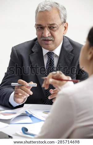 Mature businessman talking business with female executive - stock photo