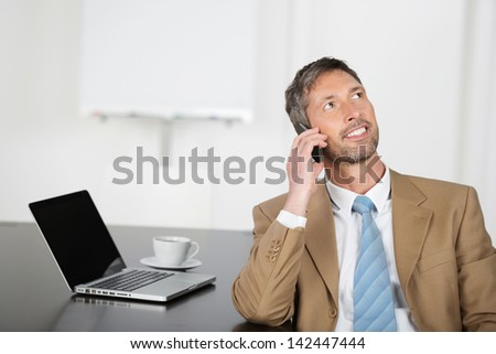 Mature businessman using mobile phone while looking up at office desk - stock photo