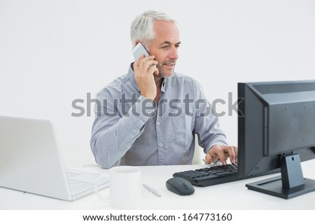 Mature businessman with cellphone, laptop and computer at desk against white background