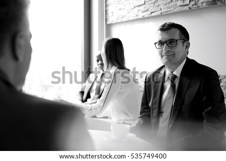 Mature businessman with colleagues in office cafeteria