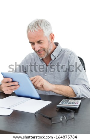 Mature businessman with digital tablet and calculator at desk against white background - stock photo