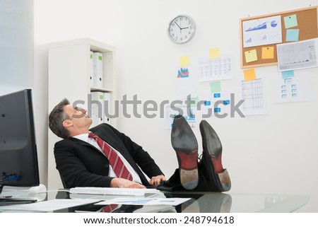 Mature Businessman With Feet On Desk Looking At Time In Office - stock photo