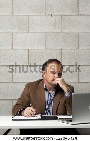 Mature businessman with hand on chin looking at laptop screen while at work