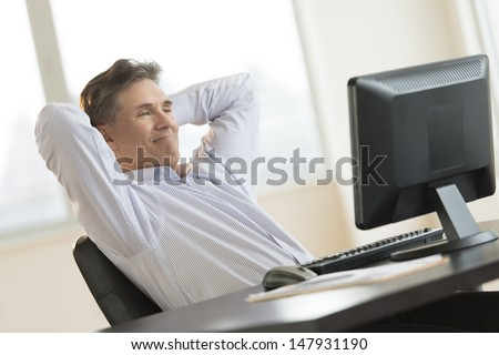 Mature businessman with hands behind head relaxing while looking at Desktop PC in office - stock photo
