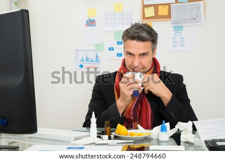 Mature Businessman With Muffler Around His Neck Drinking Lemon Tea - stock photo
