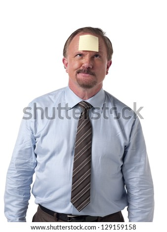 Mature businessman with stick note on forehead standing over white background