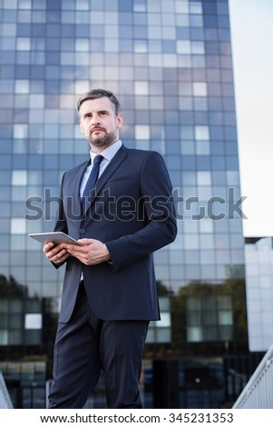 Mature businessman with tablet outside his office
