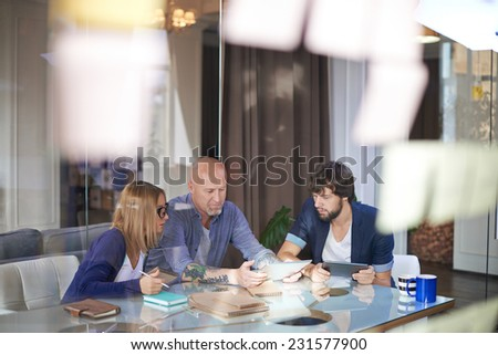 Mature businessman with touchpad presenting his colleagues fresh ideas - stock photo