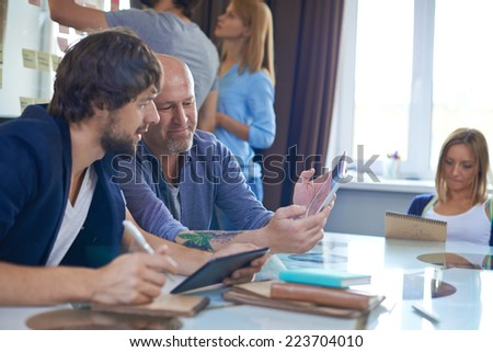 Mature businessman with touchpad showing his colleague ideas for new project - stock photo