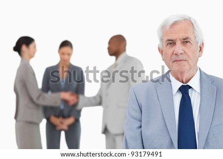 Mature businessman with trading partners behind him against a white background - stock photo