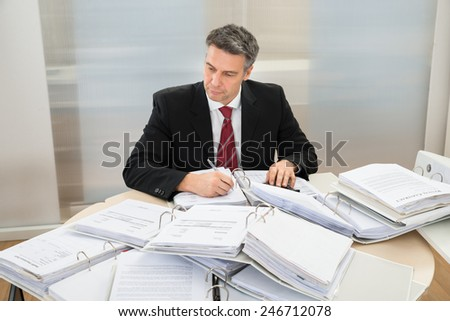 Mature Businessman Working At Office With Heap Of Folders Around Him - stock photo