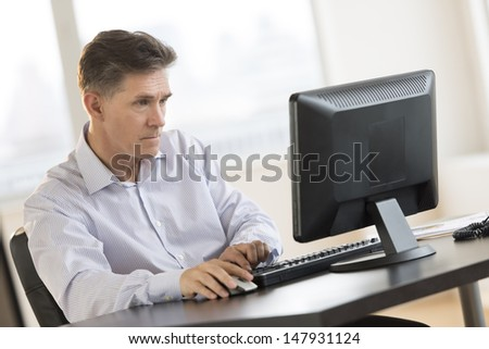 Mature businessman working on computer at desk in office - stock photo