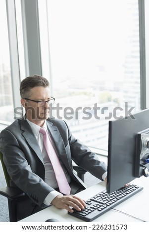 Mature businessman working on computer in office