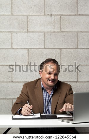 Mature businessman working on his desk with brick wall in the background