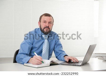 mature businessman working on his laptop in the office - stock photo