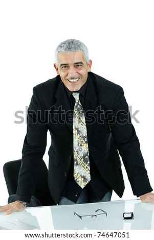 Mature businessman working on laptop computer at desk az office, smiling, isolated on white background.?