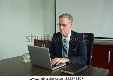 Mature businessman working on laptop in the office