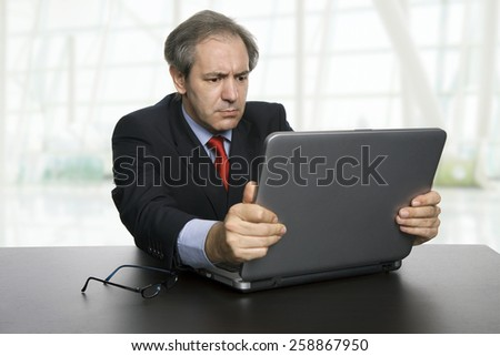 mature businessman working with his laptop, at the office - stock photo