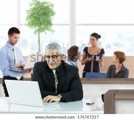 Mature businessman working with laptop in office hallway.