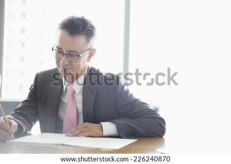 Mature businessman writing on book at table in office - stock photo