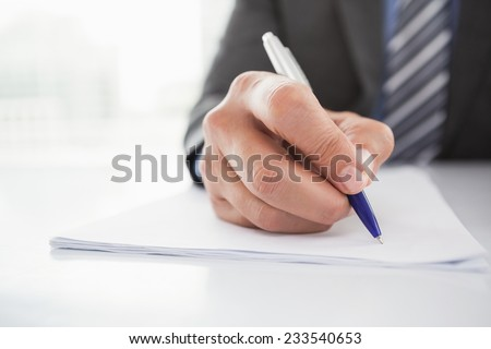 Mature businessman writing on document in his office