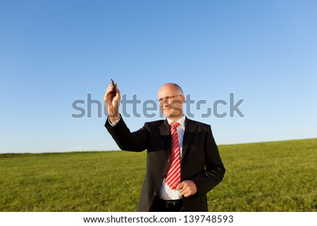 Mature businessman writing on invisible screen with marker on field against clear sky