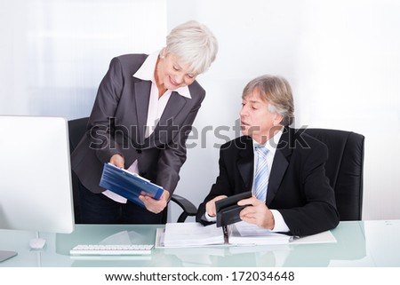 Mature Businesswoman And Businessman Discussing In Office - stock photo