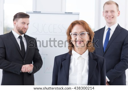 Mature businesswoman and two young businessmen in the background