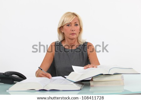 Mature businesswoman at a desk - stock photo