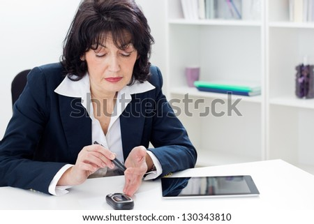 Mature businesswoman Checking Her Blood Sugar Level  in the office. Shallow dof. - stock photo